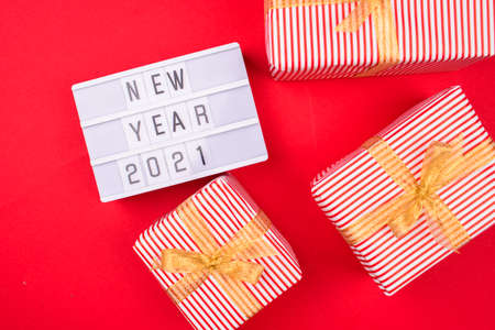 Light box with inscription new year 2021 and beautiful gifts, in a beautiful package and decor on a red background.