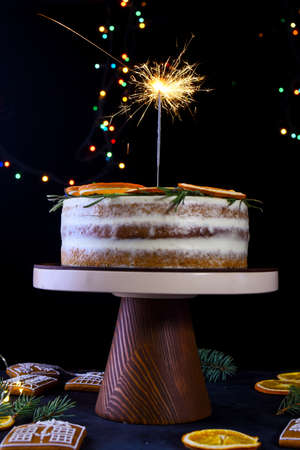 Beautiful delicious cake with sprigs of rosemary and orange frips. New Years dessert. Biscuit cakes, Standard-Bild