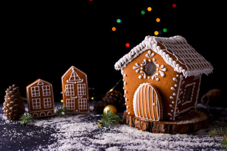 Winter gingerbread house with light from the windows, gingerbread city, big side lights, snow. New Years content. Standard-Bild