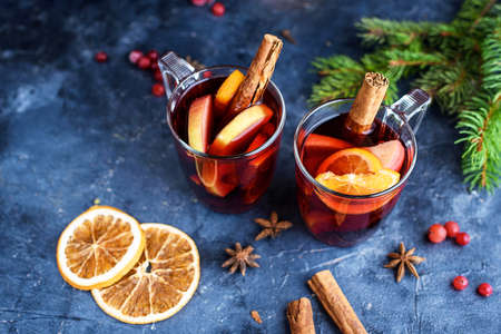 Two cups of christmas mulled wine or gluhwein with spices and orange slices on rustic table top view. Traditional drink on winter holiday