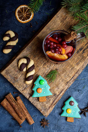 Hot Mulled Wine for winter and Christmas on wooden table with copy space. Red Hot wine. Christmas tree gingerbread