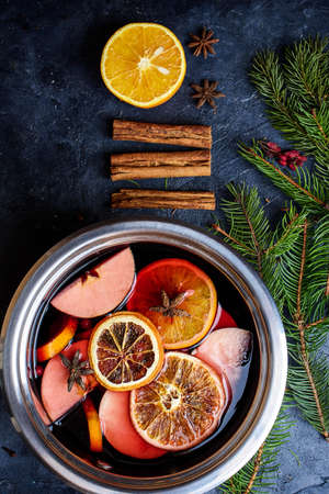 Making hot alcohol, mulled wine for sale at country fair. Glintwine from red wine with citrus and cloves in big metal stock pot, mixed with soup ladle. Closeup Standard-Bild