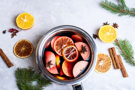 Delicious mulled wine and ingredients on grey table, flat lay. Space for text