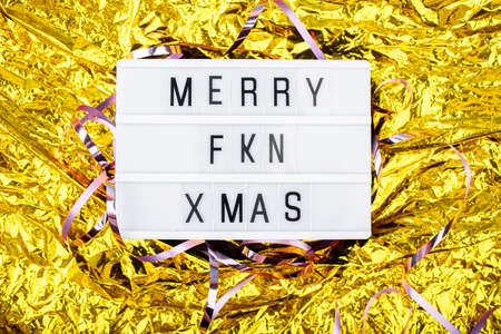 Light boxing with the words merry fkn xmas on a golden background. New Years Eve and content.