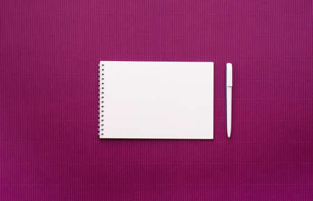 Notebook with white sheets on a spring with empty pages, white pen, light lilac background. View from above, place for text. Standard-Bild