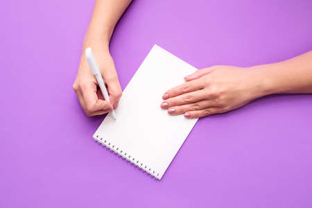 A womans hand holds a notebook with white sheets on a light background. A place for text, a view from above.