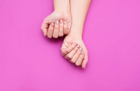 Beautiful womans hands on the pink background. Well-groomed female hands with a beautiful manicure