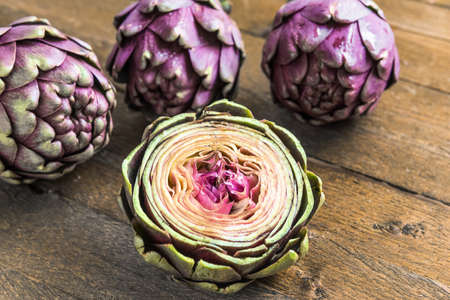 green and purple vegetables: Three large purple fresh artichoke and a half on wooden background