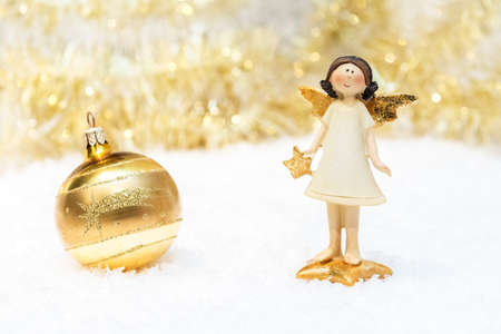 stays: The ceramic girl-angel stays on the snow with gold Christmas ball