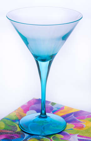 Empty light blue cocktail glass staying on bright multicolored napkin on white background photo