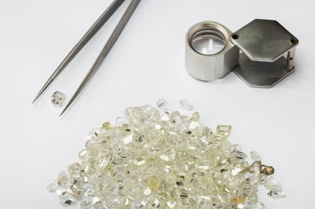 priceless: Diamonds, pair of tweezers and magnifier glass on white background