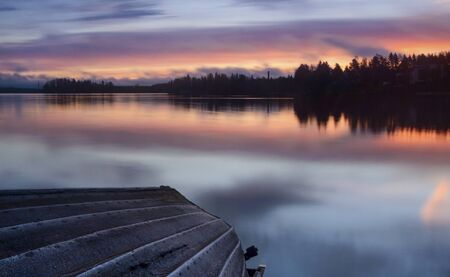 A fishing boat on the shore during sunrise