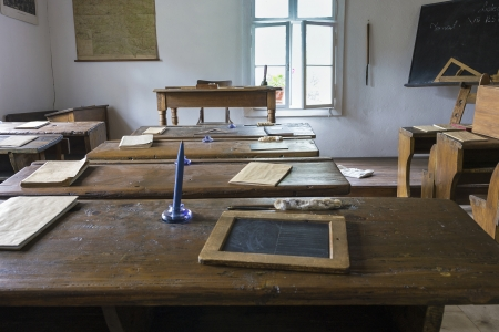 Tables, exercise books, candles in old classroom interior photo
