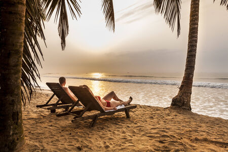 Couple on the sunbeds on the tropical beach in Africa