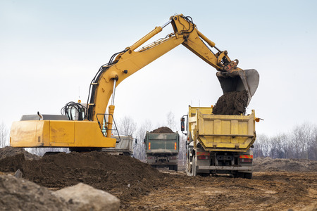 Building Machines  Digger loading trucks with soil Stok Fotoğraf - 26979313