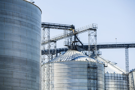 Huge, silver, shiny agricultural silos. Stock Photo