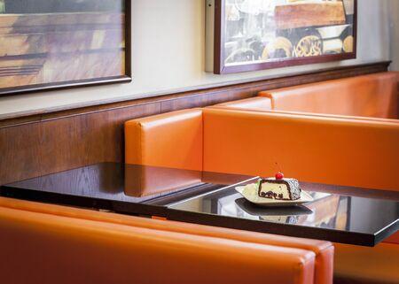 invitando: Invitar a comer pastel con la cereza en un lugar cafe Foto de archivo