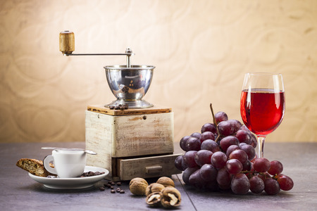 Still life of coffee grinder, coffee and sweet Italian cookie cantuccini, grapes and glass of wine