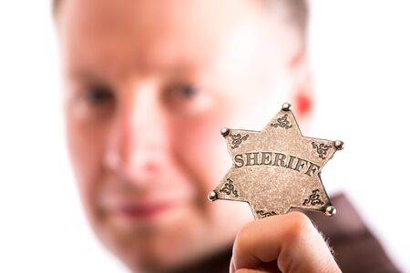 lawman: Man holds sheriff badge isolated on white background