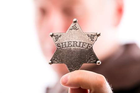 sheriff badge: El hombre sostiene insignia de sheriff aisladas sobre fondo blanco