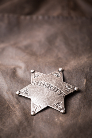 Close up of sheriff badge when on his coat duster