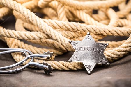 sheriff badge: Insignia de sheriff, espuelas y lazo. S�mbolo occidental.