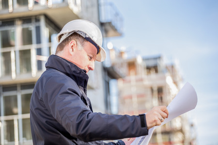 Construction manager with blueprints standing in front of construction site. Stok Fotoğraf