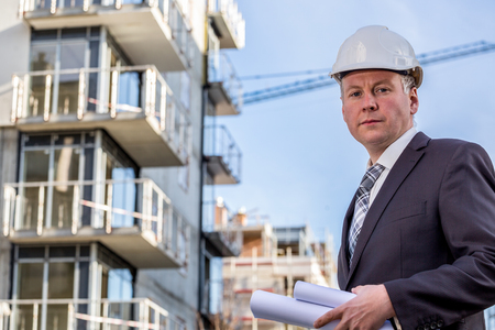 construction manager: Construction manager with rolled up blueprints standing in front of construction site.