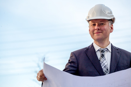 construction manager: Construction manager with blueprints standing in front of construction site. Stock Photo
