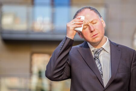 Stressed businessman having headache outside the office