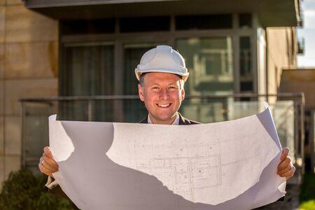 construction manager: Construction manager with blueprints standing outdoor .