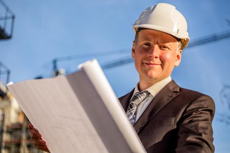 gestionnaire de la construction avec les plans debout devant chantier de construction.