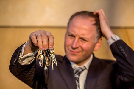 Businessman choosing the right key among bunch photo