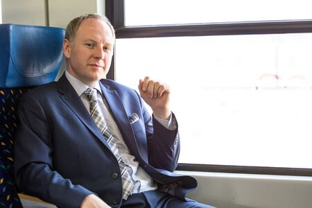 navy blue suit: Businessman sitting in a train and thinking