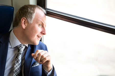 Businessman surprised what he sees through trains window Stock Photo