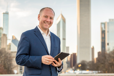 Businessman with tablet in front of skyscrapers Stok Fotoğraf