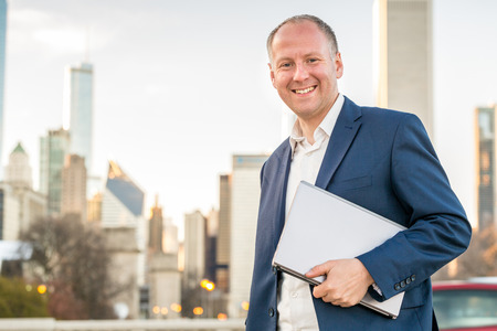 navy blue suit: Businessman with laptop in front of skyscrapers Stock Photo