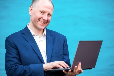 easy going: Young businessman with his laptop against turquoise wall