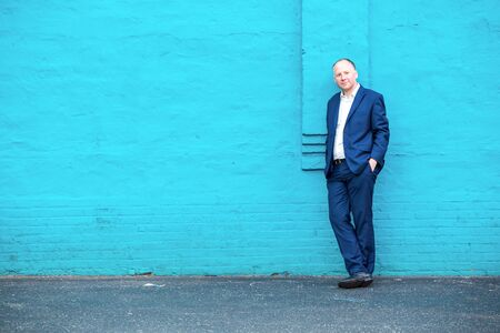 navy blue suit: Thinking businessman and turquoise copy space.
