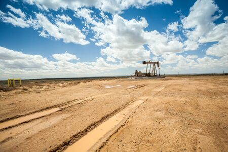 space weather tire: Oil pump jack surrounded by flat desert