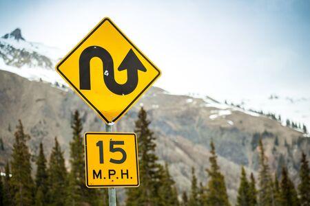 mph: Curvy road sign an 15 m.p.h speed limit