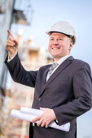 overseer: Construction manager with blueprints at the construction site