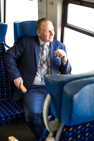considerate: Businessman sitting in a train and thinking