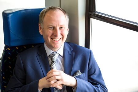 navy blue suit: Businessman sitting in a train and enjoying his travel