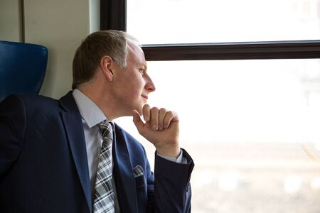 wondered: Businessman interested in what he sees through window during his trip