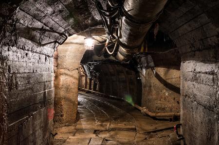 gold mining: Real underground post mine illuminated tunnel .