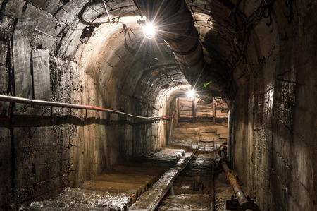Real underground post mine illuminated tunnel .