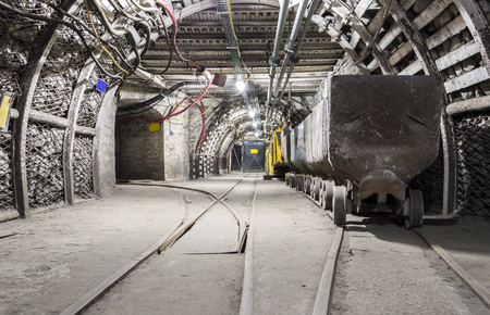 tunneling: Mining carriage in underground illuminated tunnel .
