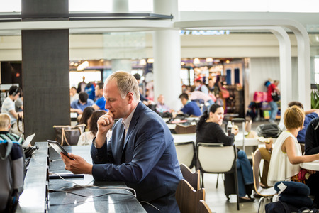 Businessman using his tablet waiting at the airport Standard-Bild
