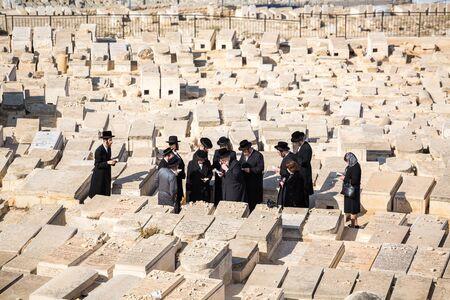 jews: Jerusalem, Israel - November 1, 2015: Orthodox Jews praying on the Mount of Olives cemetery.